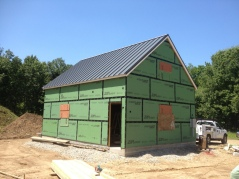 Metal roof complete on the garage, window openings boarded up. Garage windows should arrive shortly.